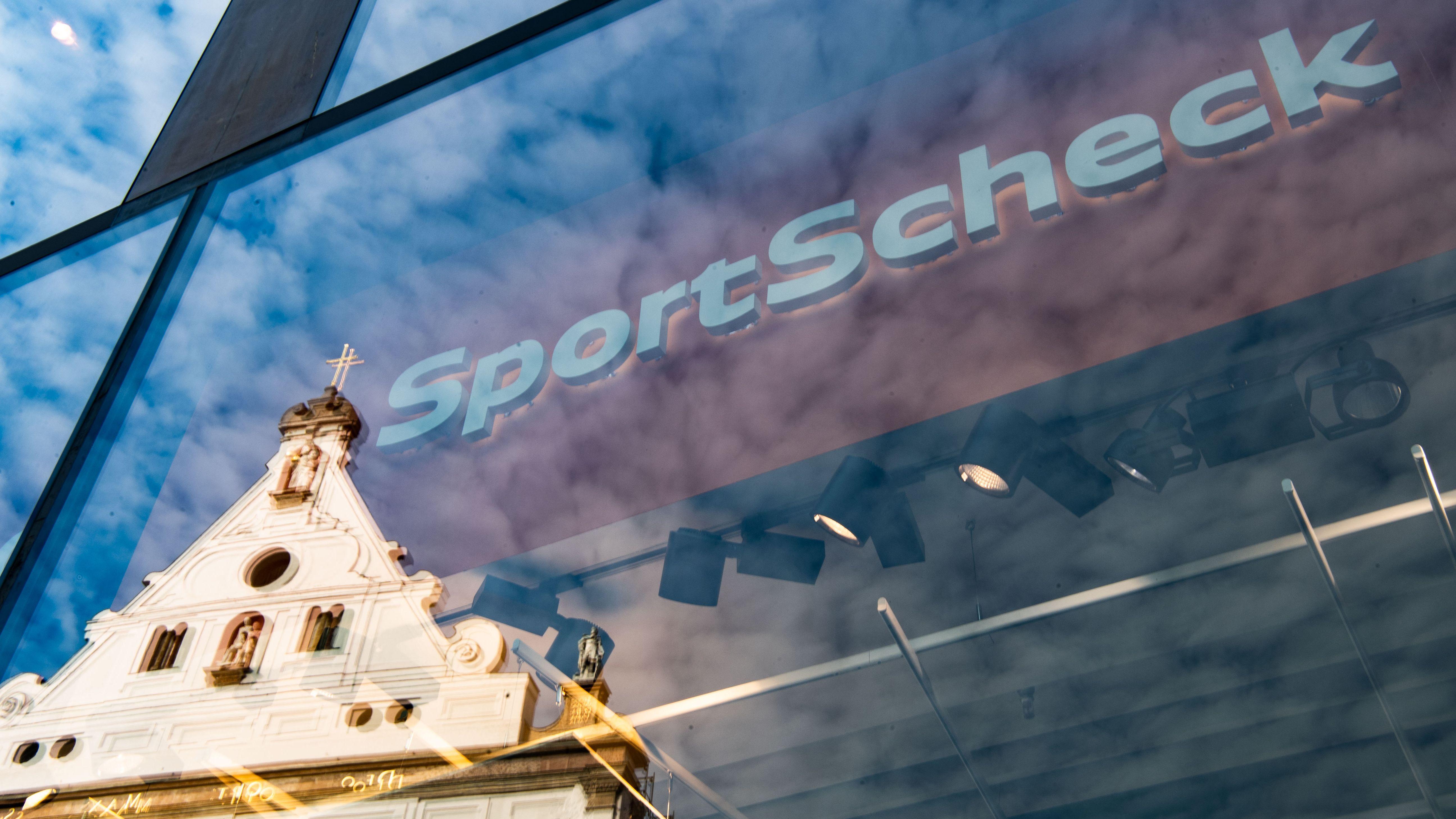 In der Fassade einer Sport Scheck-Filiale in der Münchener Fußgängerzone spiegelt sich ein Haus.