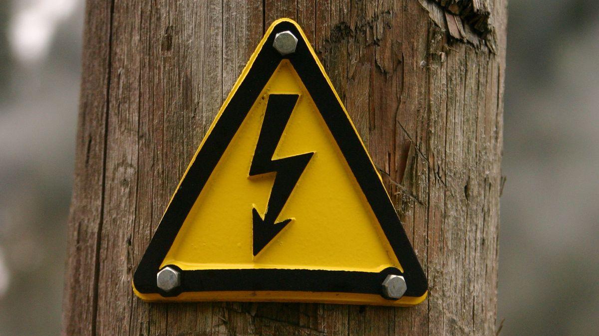 """Symbolbild: Gelbes Schild mit gezacktem schwarzem Pfeil """"Achtung Strom""""."""