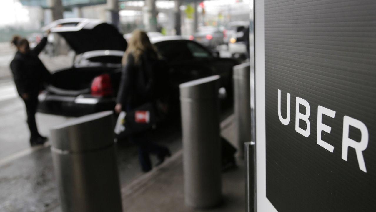 Ein Schild mit dem Logo des amerikanischen Dienstleistungsunternehmens Uber steht am Abholpunkt von Uber auf dem LaGuardia-Flughafen in New York.