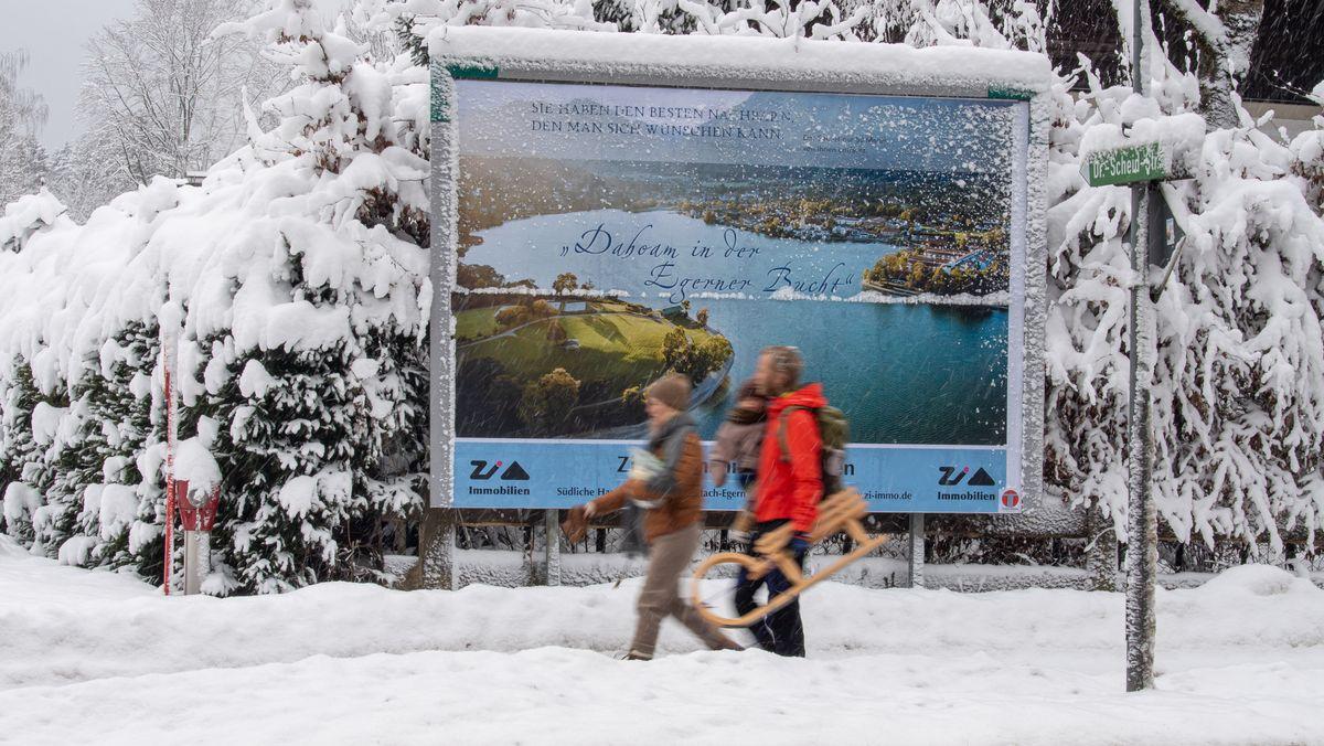 Ein Pärchen mit Kind und Schlitten läuft durch den Schnee an einem Werbeplakat vorbei, das den Tegernsee aus der Luft im Sommer zeigt.