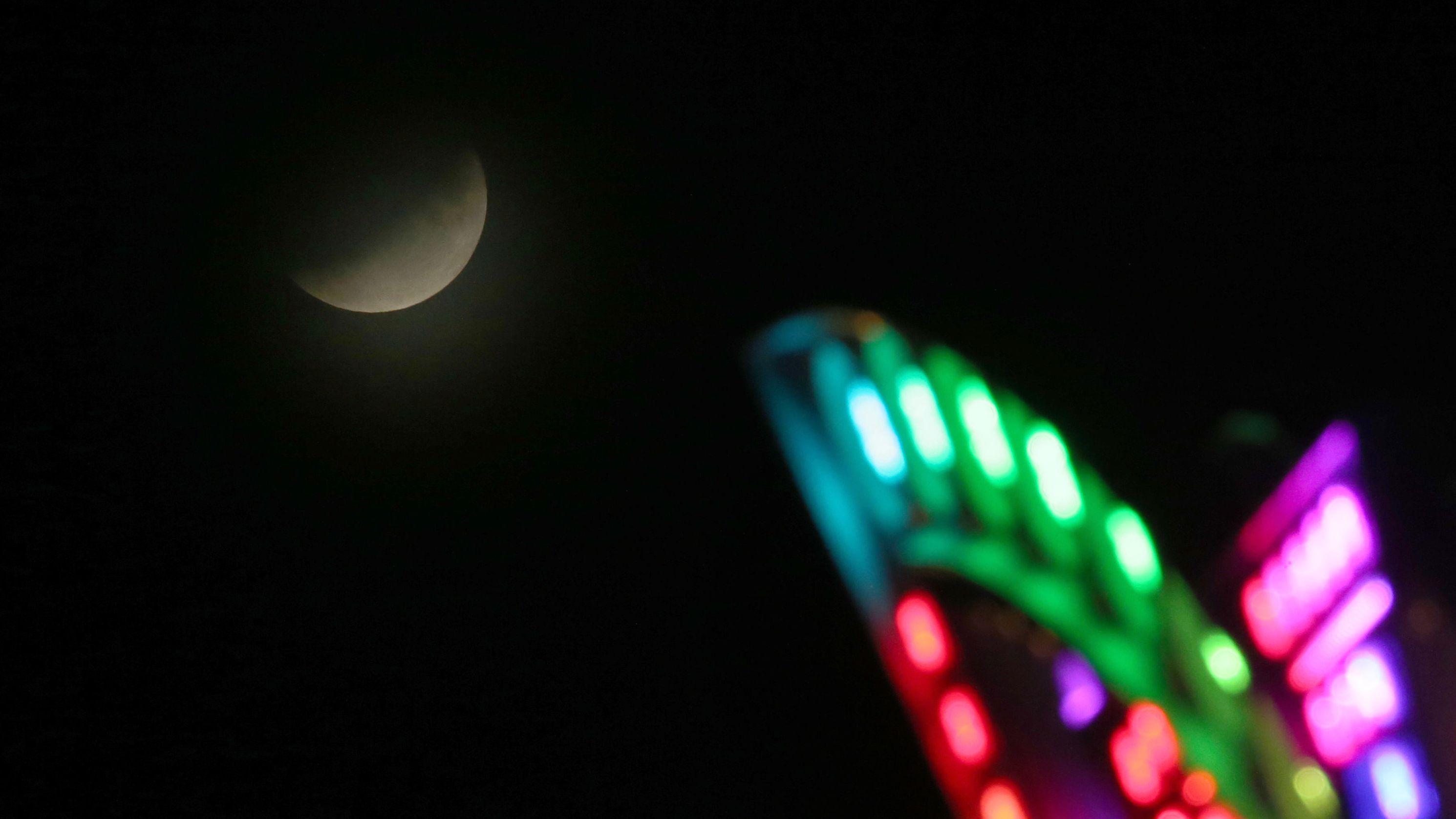 Würzburg: Der Mond ist während einer partiellen Mondfinsternis ist hinter einem Fahrgeschäft des Kiliani-Volksfestes zu sehen.