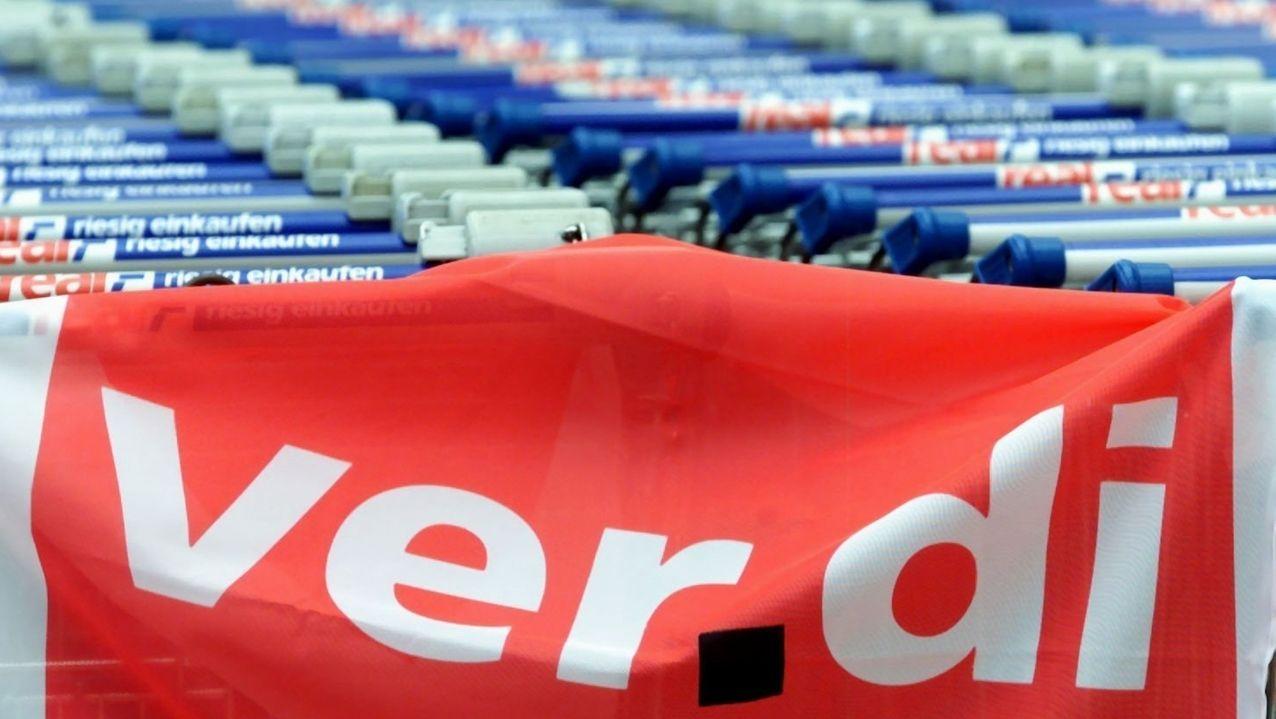 Symbolbild: Verdi-Fahne vor Einkaufswagen