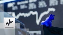 ein blauer Stier aus Gummi sitzt auf der oberen Kante eines Bildschirmes, im Hintergrund die Kurstafel der Börse   Bild:BR / Philipp Kimmelzwinger