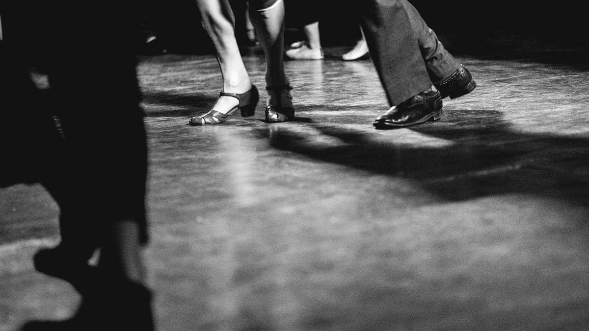 Eine schwarzweiß Aufnahme tanzender Füße mit männlichen und weiblichen Schuhen