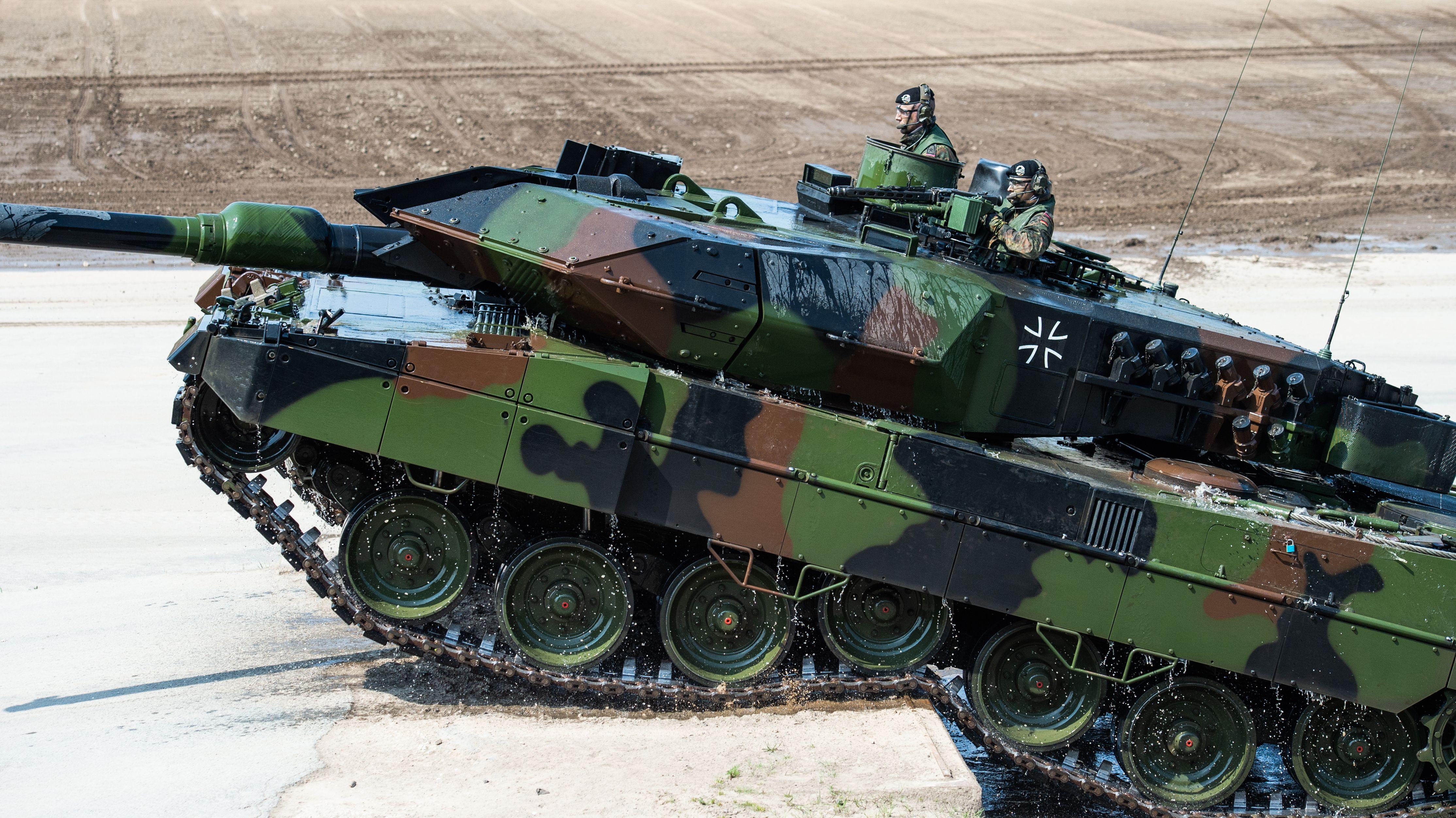 Ein Kampfpanzer Leopard 2 fährt über eine Stufe.