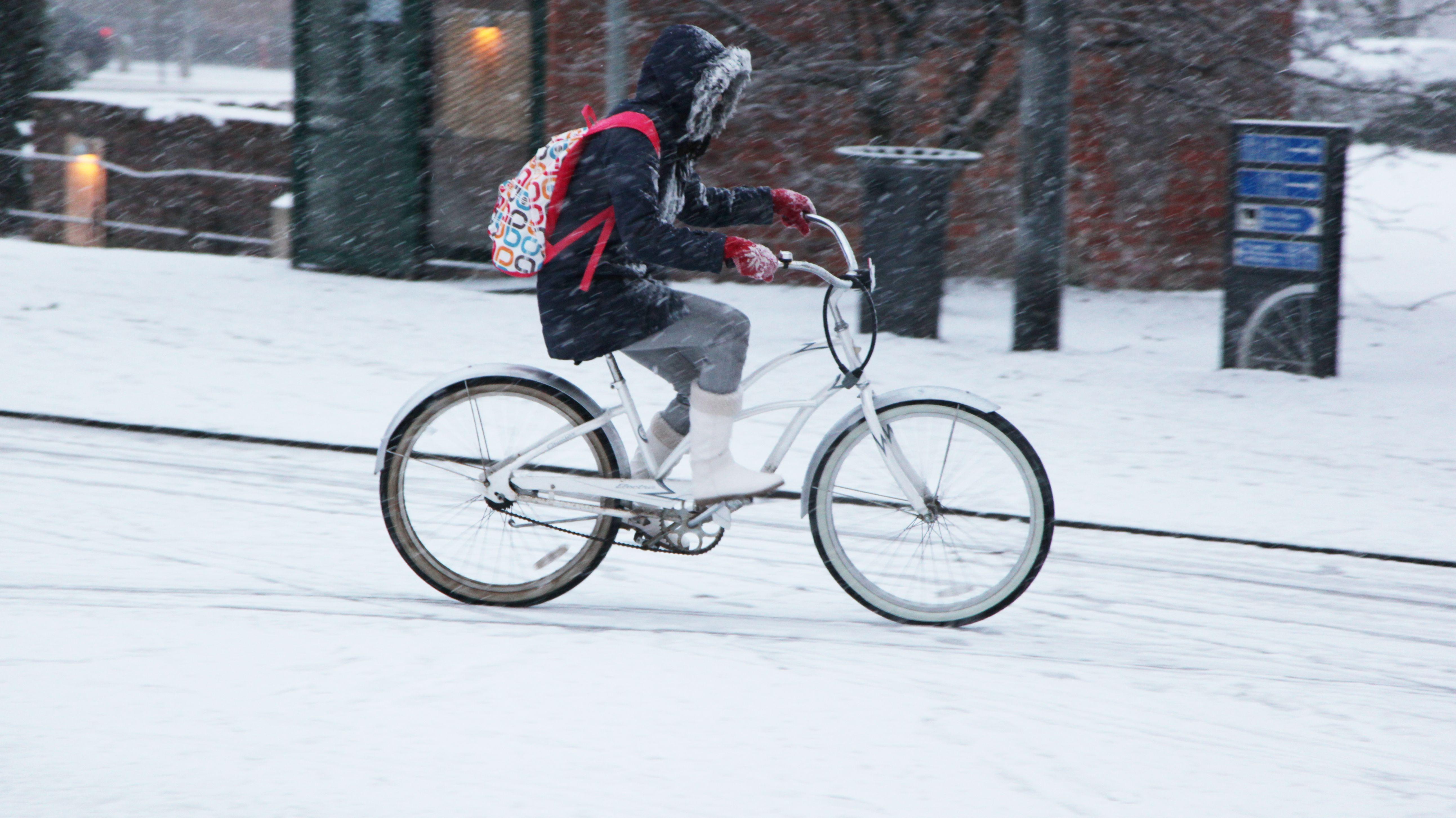 Mädchen auf einem Fahrrad auf verschneiter Straße