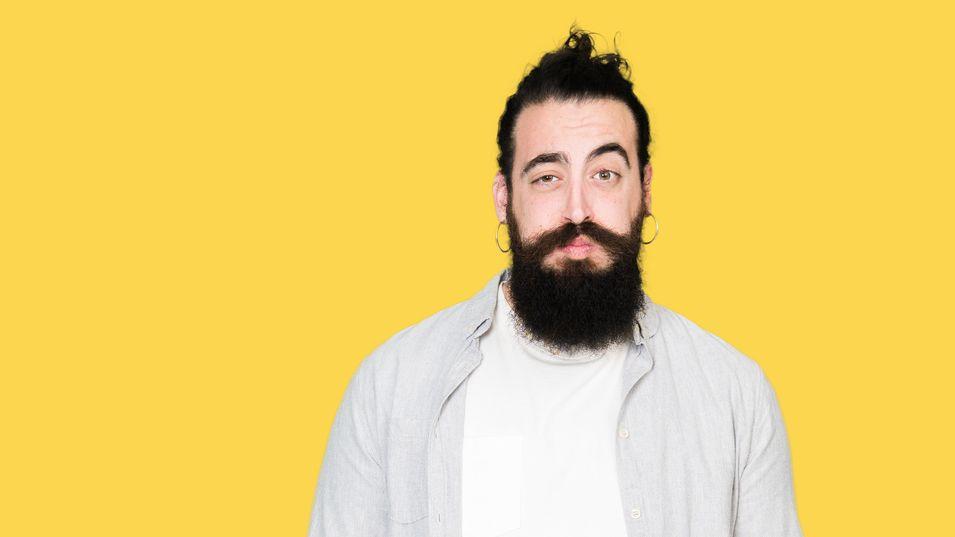 Ein Mann mit Bart vor gelbem Hintergrund.