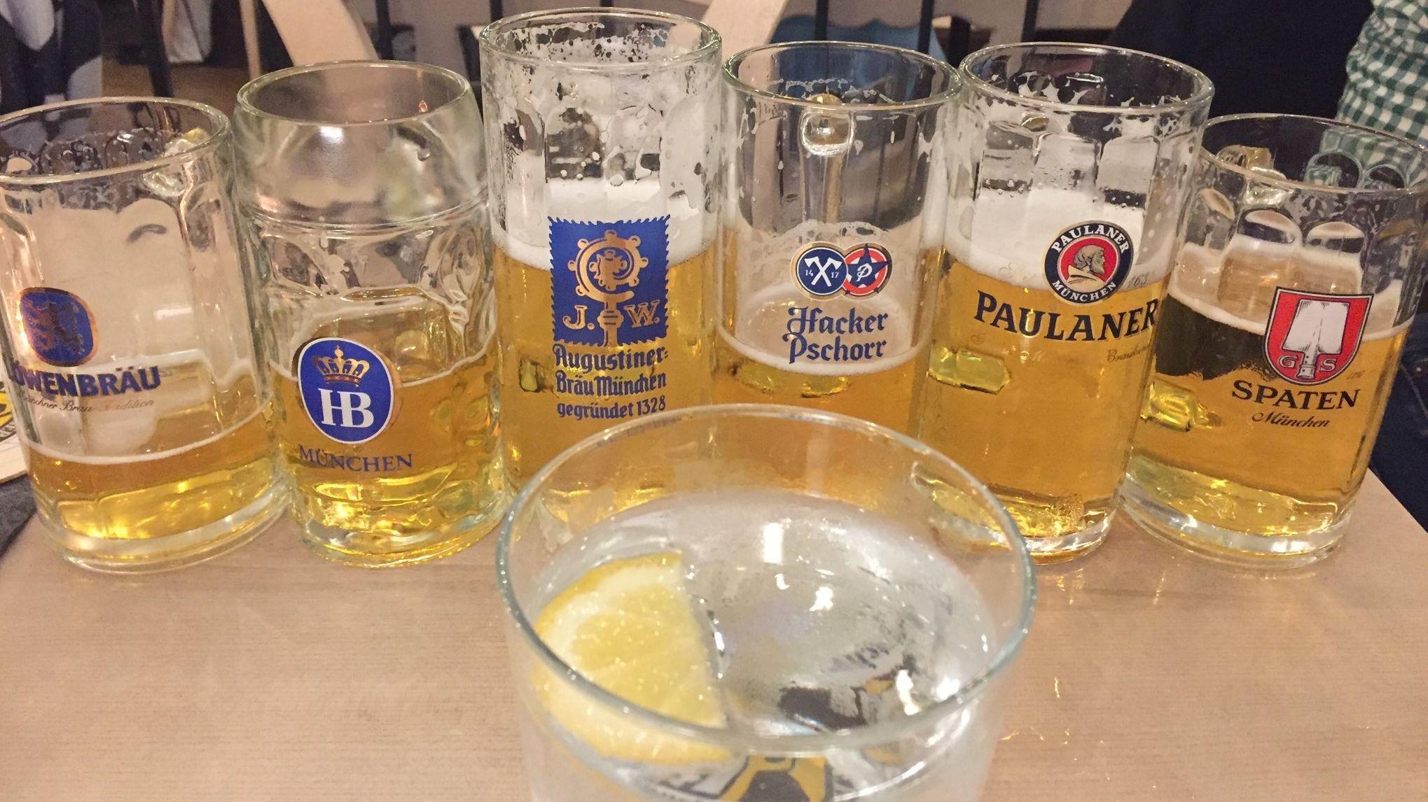 Sechs halbgefüllte Bierkrüge der Münchner Brauereien und ein Glas Wasser