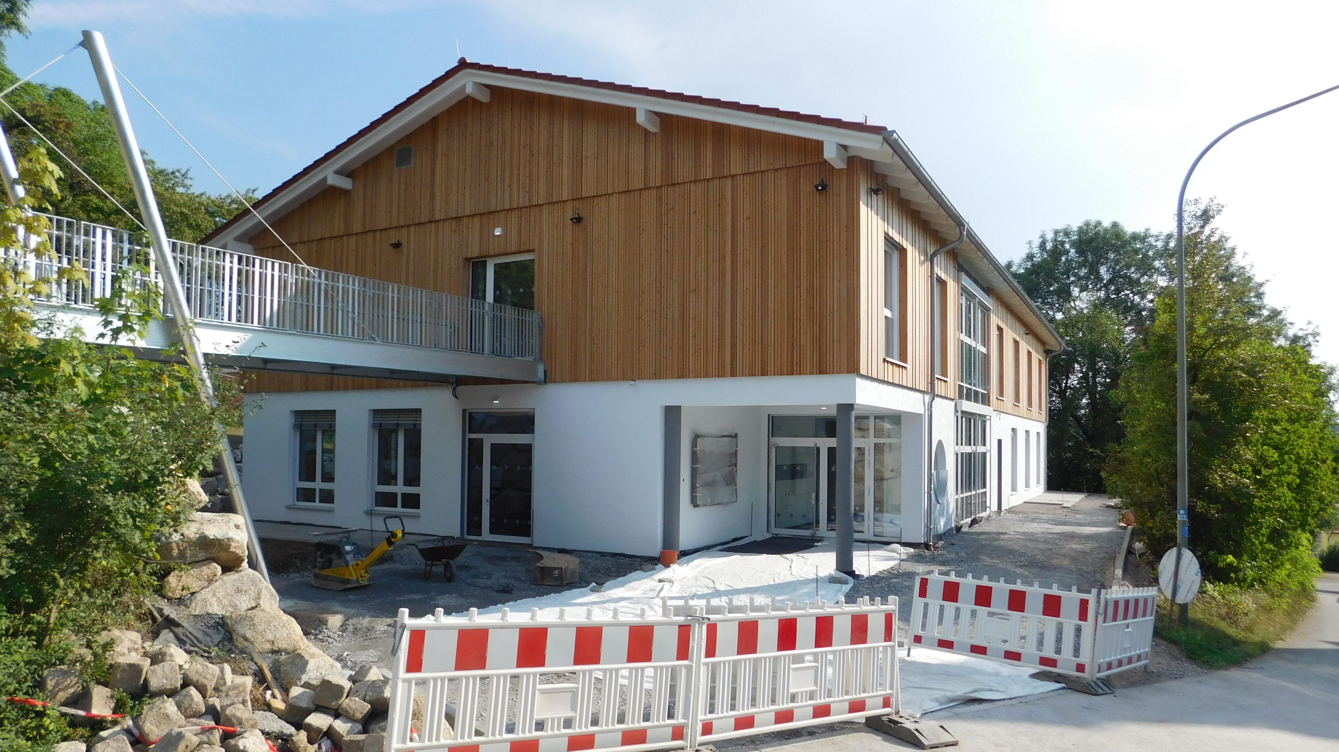 Die neue Jugendstätte in Haidenaab, die Fassade des Obergeschosses ist mit Holz verkleidet. Davor ist eine rot-weiße Absperrung, daneben Pflastersteine, die noch verlegt werden müssen.