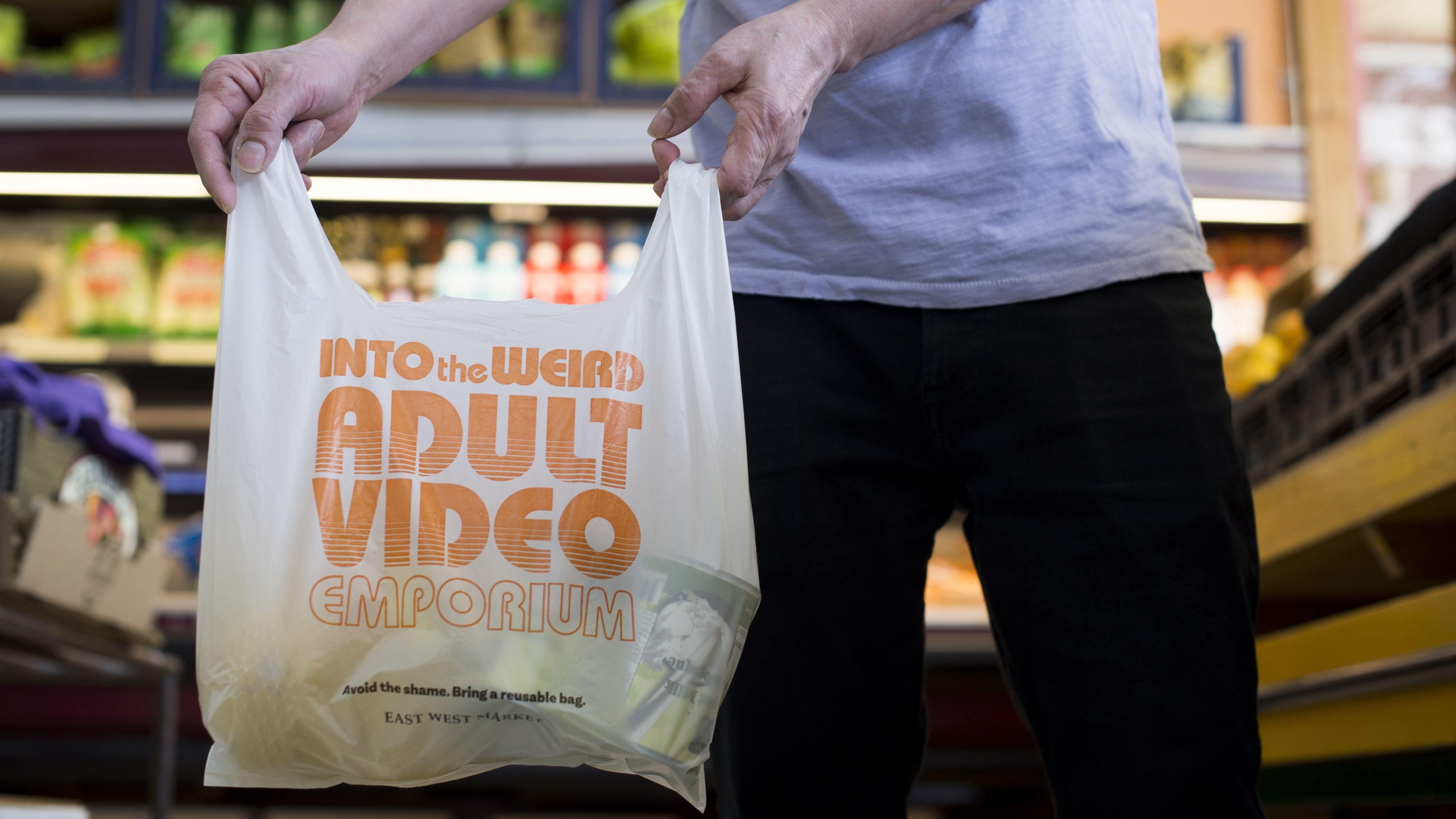 Mann hält in Supermarkt Plastiktüte mit Werbung für einen Pornofilm-Shop.