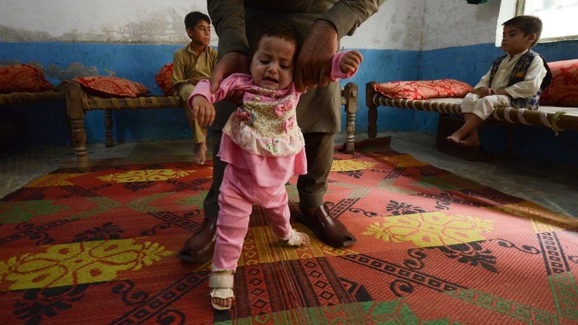 Kleines Kind kann nicht laufen und wird vom Vater gehalten