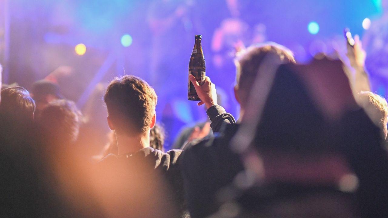 Jugendliche feiern, dabei werden auch Bierflaschen in die Höhe gehalten