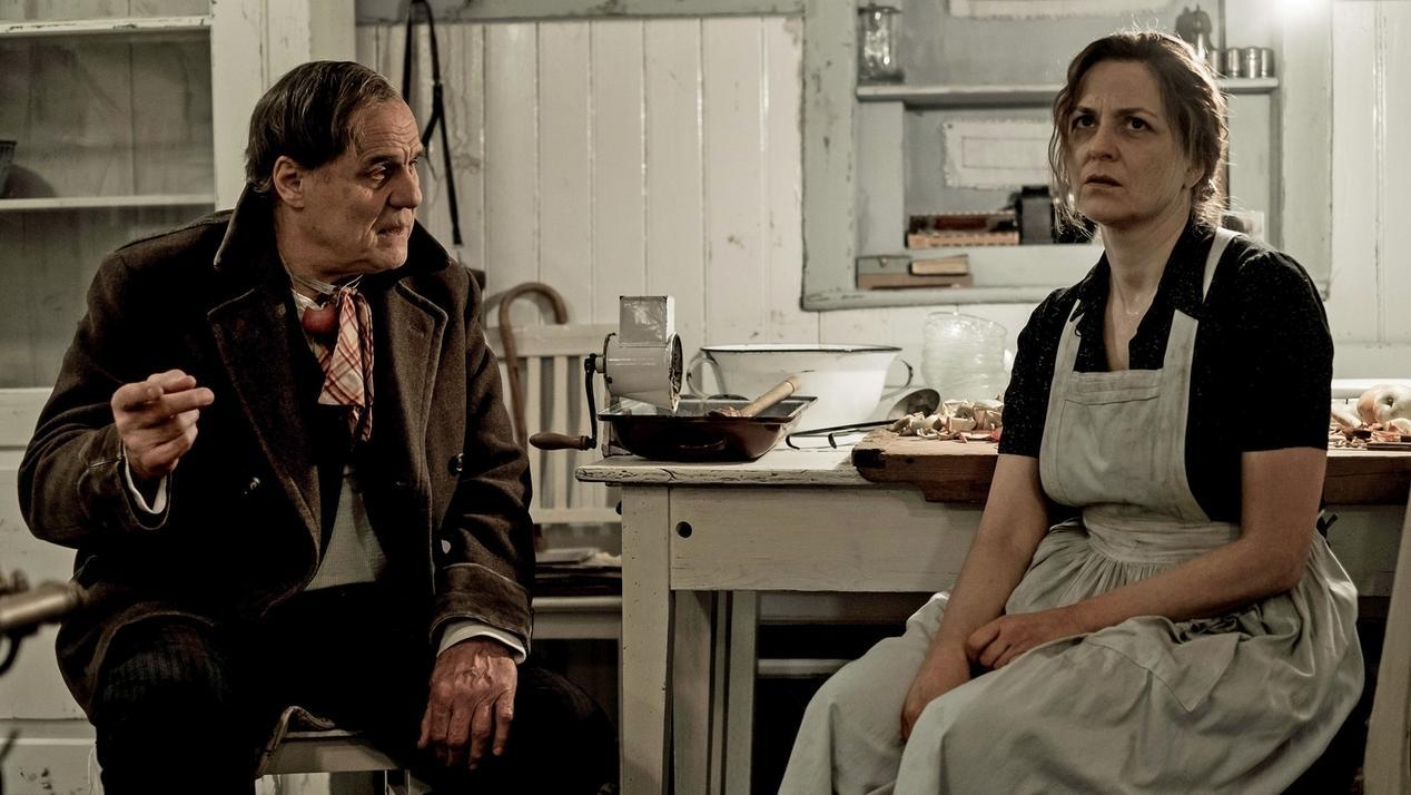 """Sepp Bierbichler und Martina Gedeck in """"Zwei Herren im Anzug"""", an einem Küchentisch sitzend"""