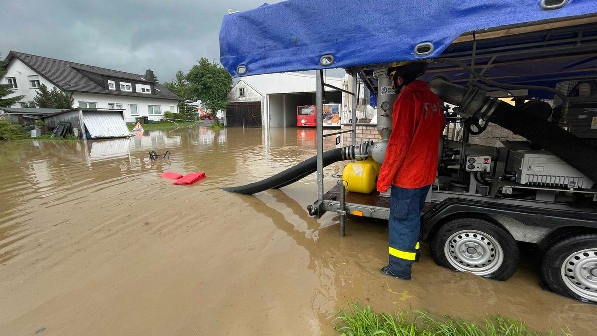 Ein Einsatzhelfer pumpt Wasser von einer überschwemmten Straße ab.