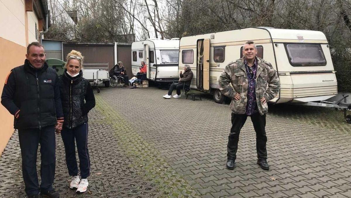 Jochen und Heike Stöckert sowie Sammy West vor zwei Wohnwagen, die auf einem Parkplatz stehen.