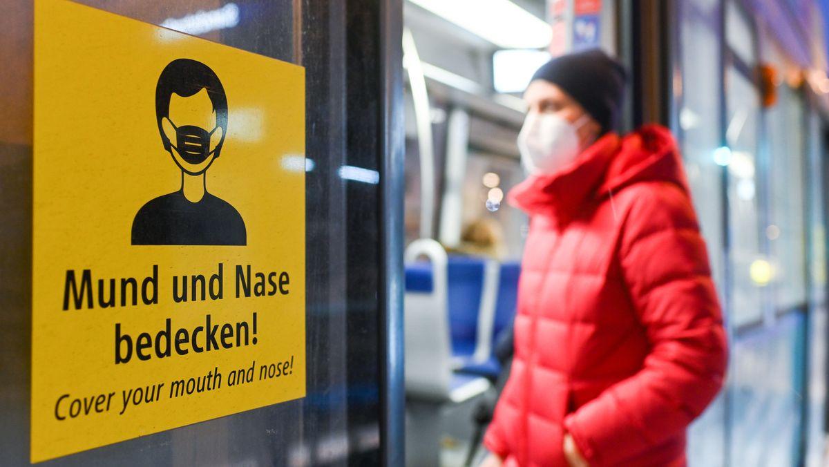 Eine Frau, die eine FFP2-Maske trägt, steigt in eine Trambahn ein.