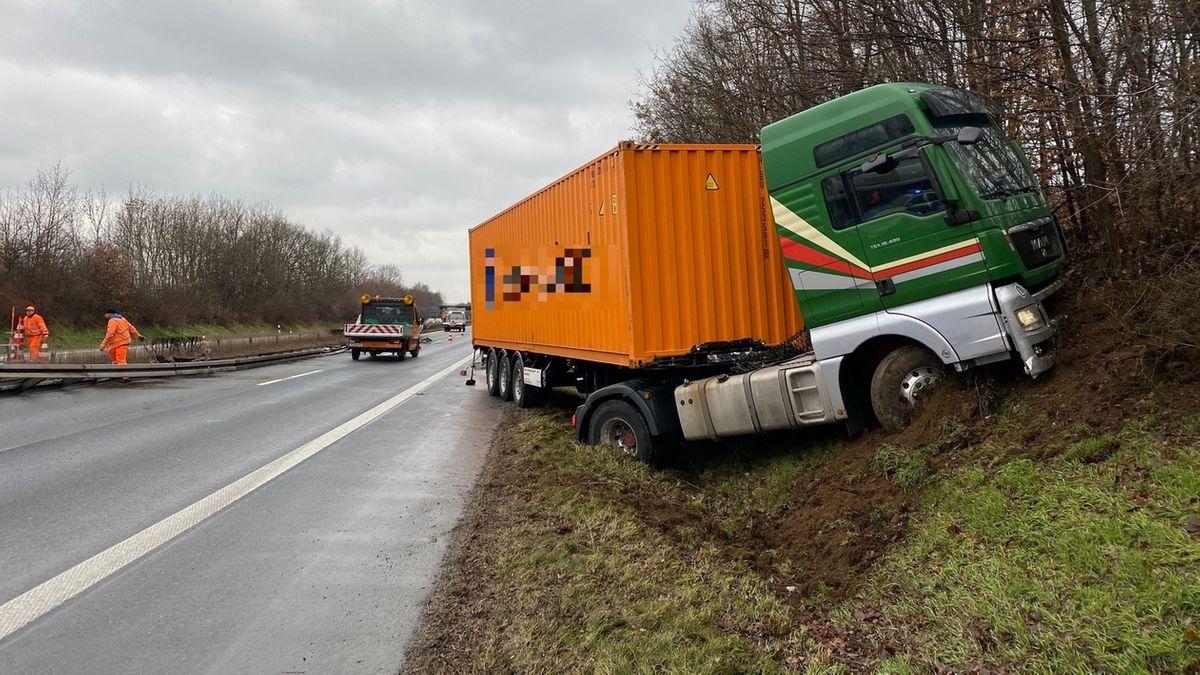 Der verunfallte, orangene Lkw steckt in der Böschung der Gegenfahrbahn fest.