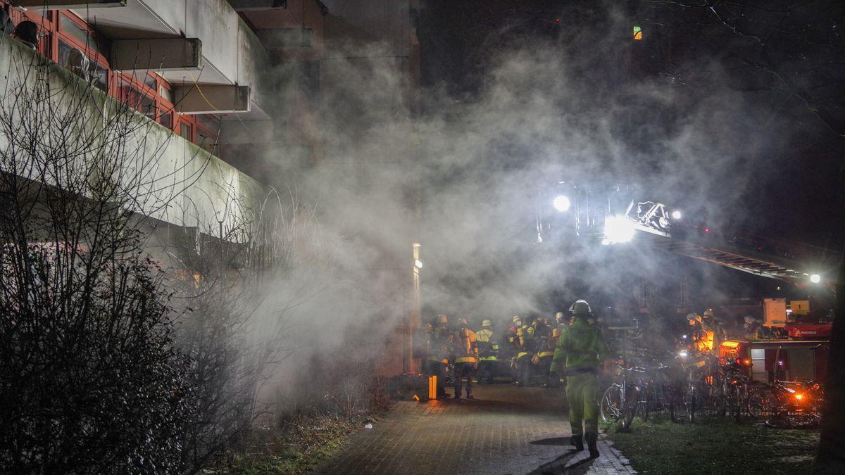 Am linken Bildrand die Fassade des Studentenwohnheims im Münchner Stadtteil Freimann. Aus dem Keller zieht dichter Rauch. Vor dem Gebäude versammeln sich in der Nacht Feuerwehrleute mit Ausrüstung, Drehleitern und Scheinwerfern.