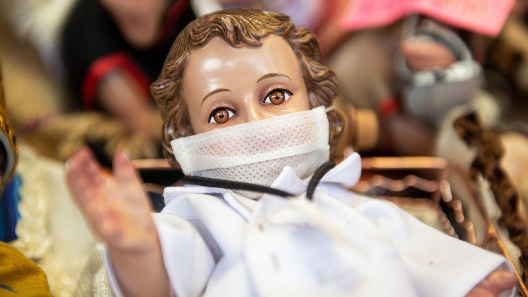 Figur eines Jesuskindes in der Krippe mit Mundschutz