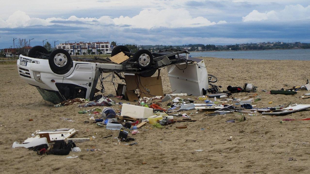 Zerstörter Camper liegt auf dem Dach am Strand