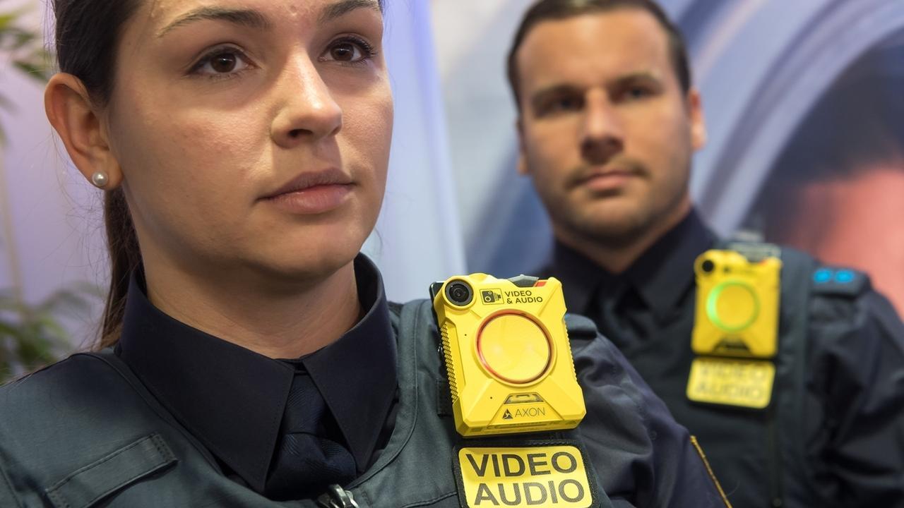 Zwei Polizisten, die eine kleine gelbe Kamera an ihrer Schulter befestigt haben