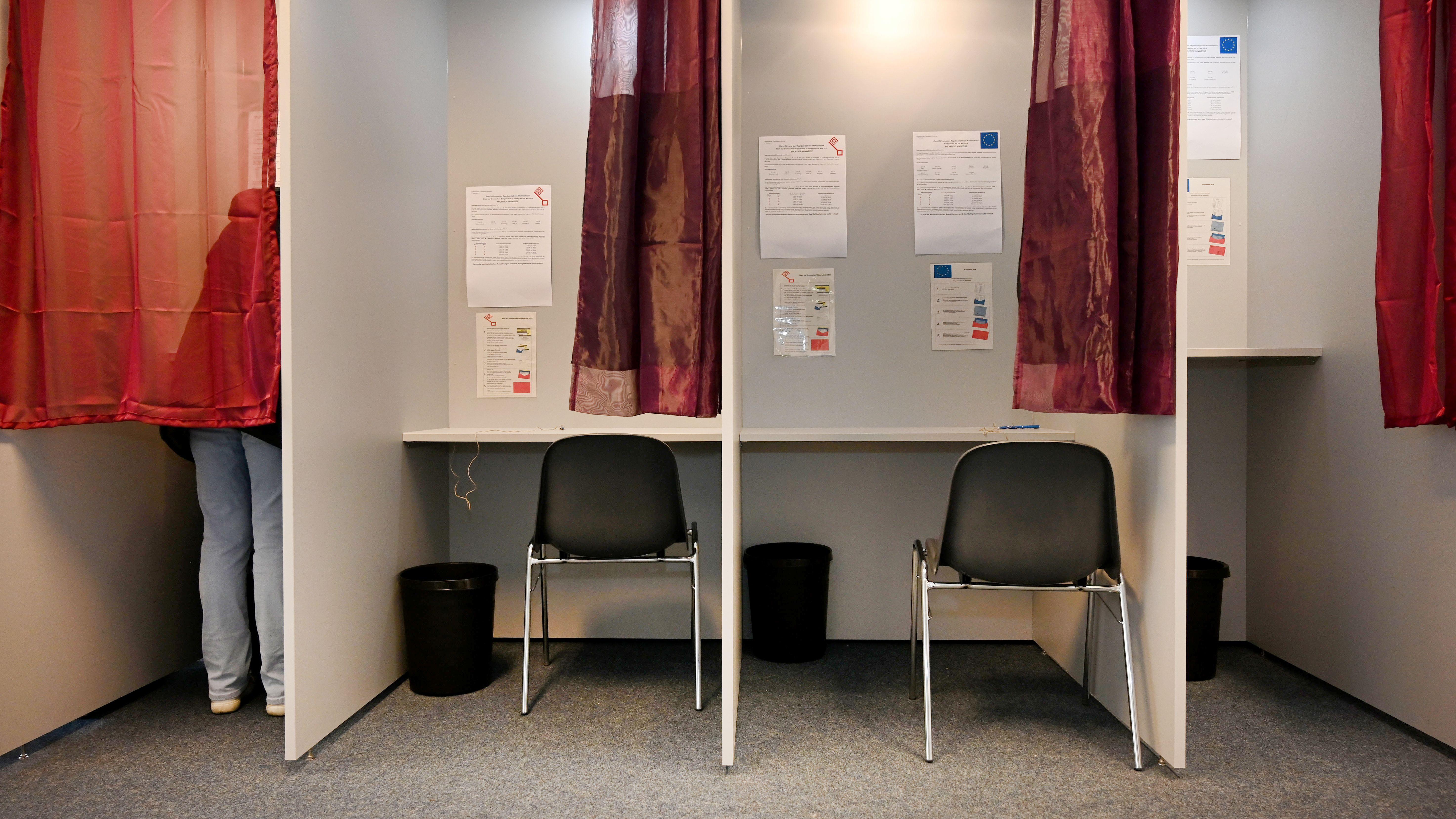 Eine Frau steht in einer Wahlkabine.