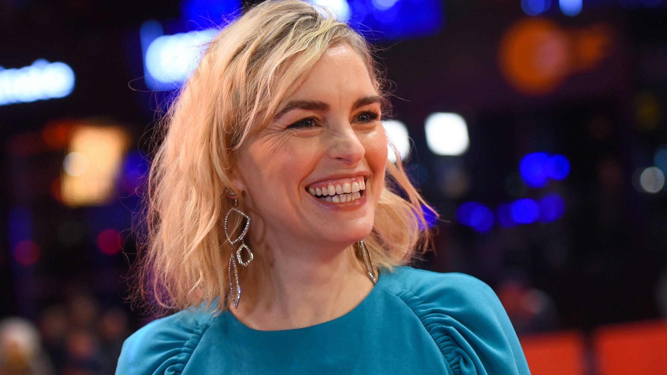 Eine Frau mit blonden Haaren und großen silbernen Ohrringen lacht neben der Kamera vorbei.