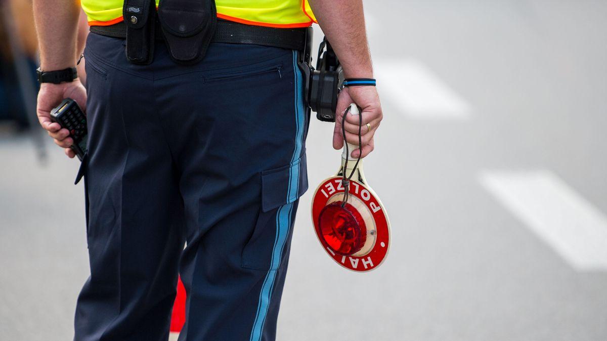 """Ein Grenzpolizist hält eine Kelle mit der Aufschrift """"Halt, Polizei""""."""