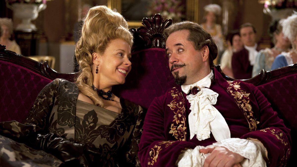 Ein Mann und eine Frau in historischen Kostümen sitzen auf einer Couch. Ausschnitt aus einem Film.