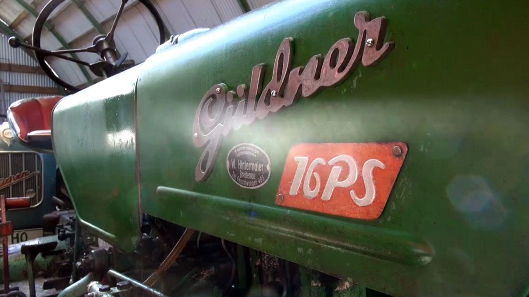 Ein grün-lackierter Traktor der Marke Güldner mit einem roten Fahrersitz und einem schwarzen Lenkrad.