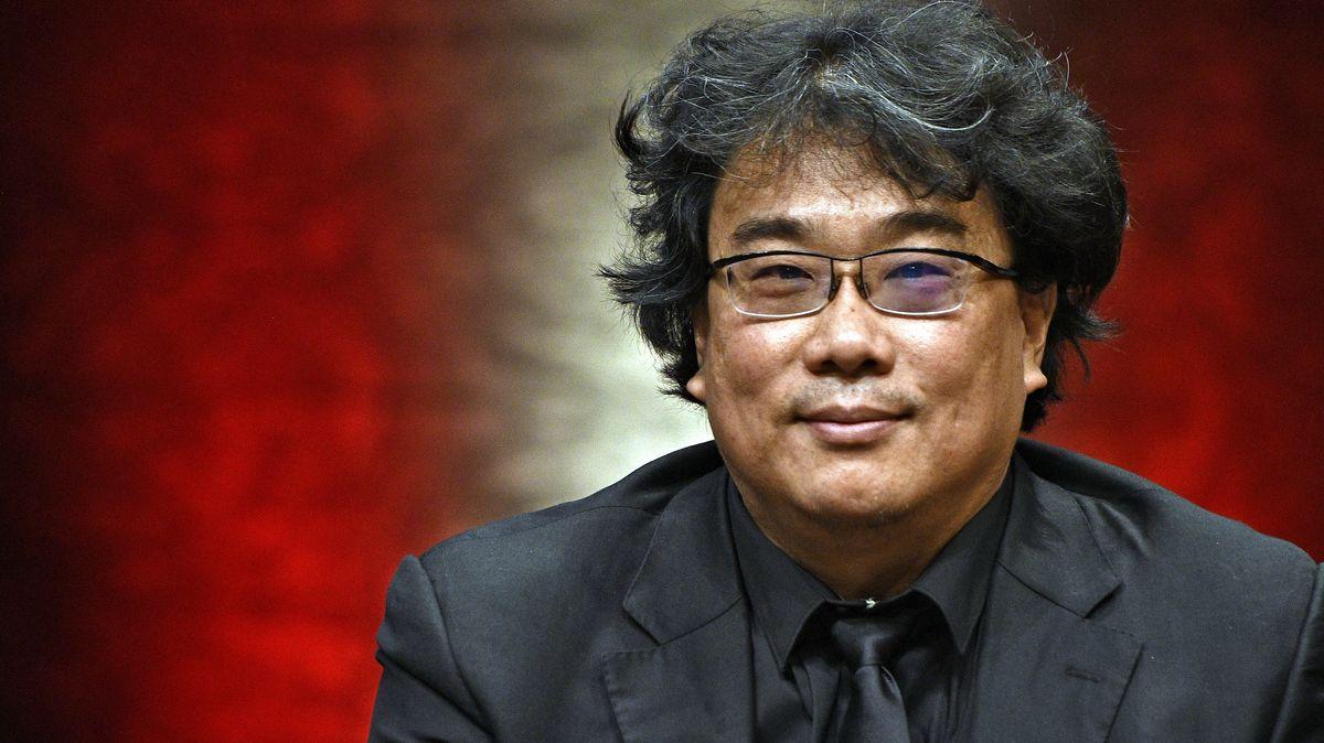 Regisseur Bong Joon-ho blickt vor rotem Hintergrund lächelnd in die Kamera