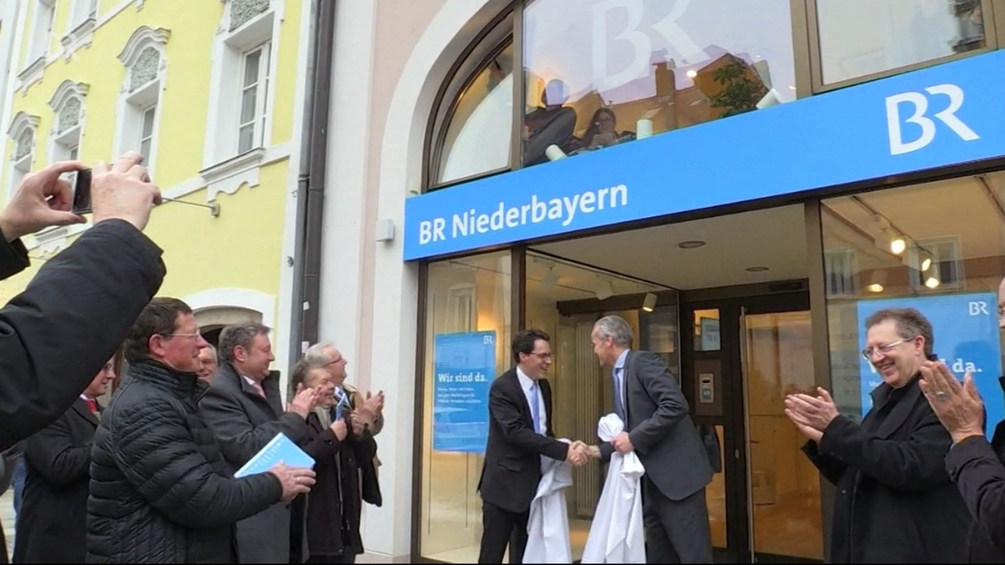 Deggendorfs Oberbürgermeister Christian Moser (CSU) und BR-Informationsdirektor Thomas Hinrichs enthüllen das Schild am Eingang des BR-Studios