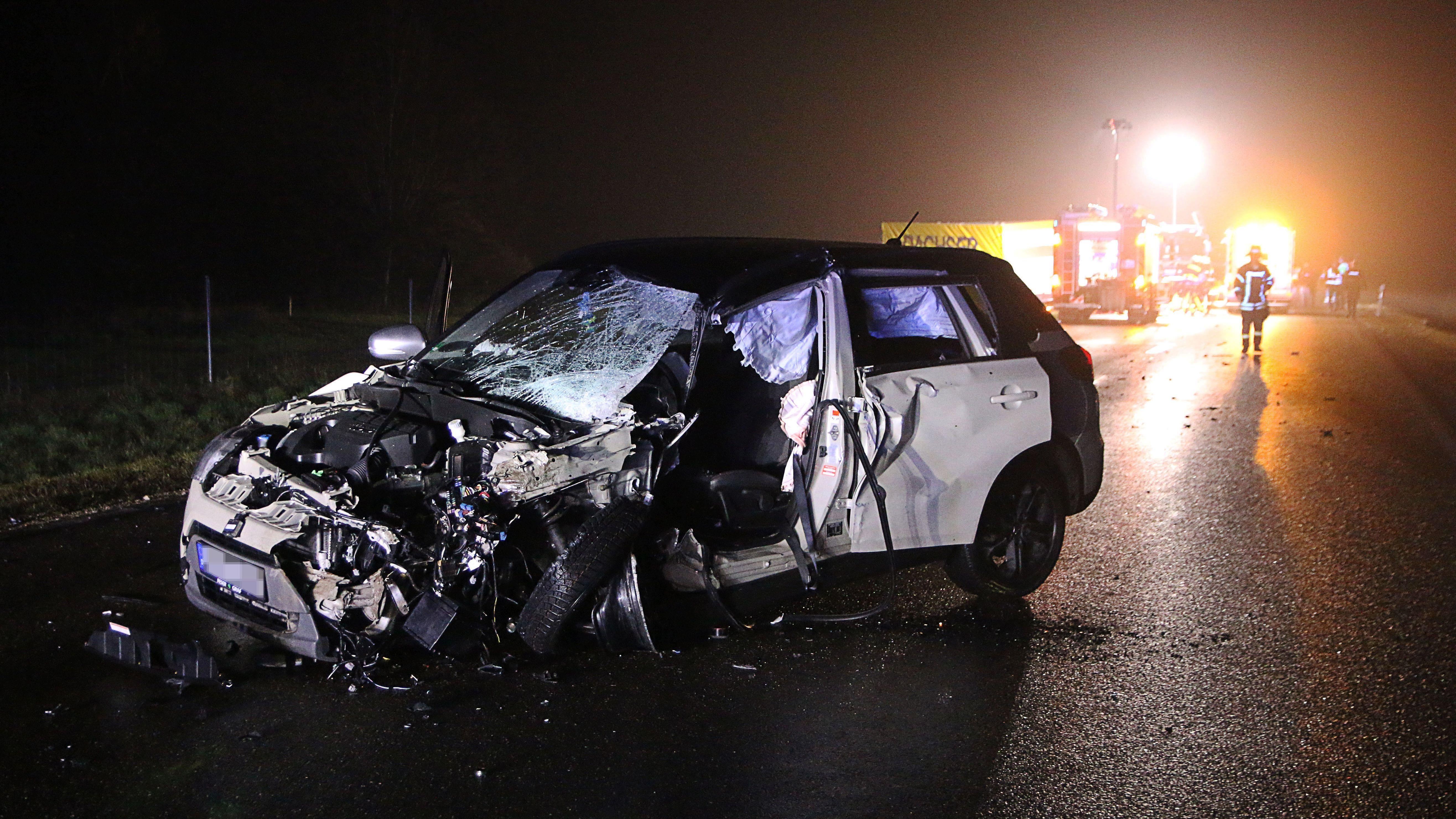 Eines der Unfallfahrzeuge im Vordergrund - im Hintergrund ein Lkw und Einsatzfahrzeuge und Kräfte der Feuerwehr