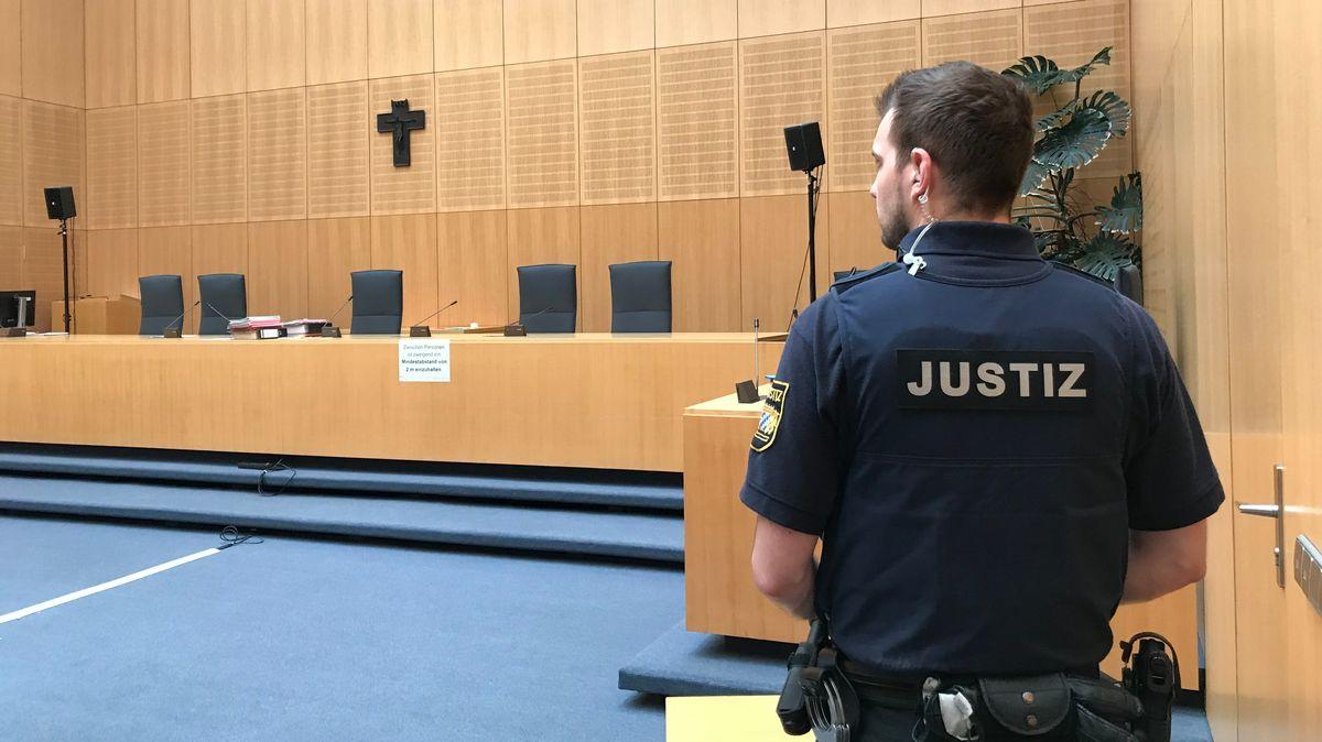 Ein Beamter der Justiz steht mit dem Rücken zum Bild in einem Gerichtssaal am Landgericht Weiden