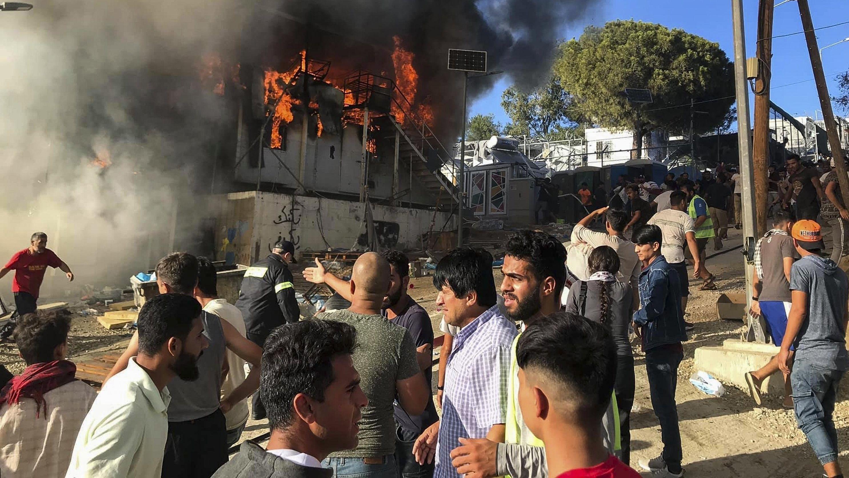 Migranten und Flüchtlinge stehen neben brennenden Hauscontainern im Flüchtlingslager Moria.