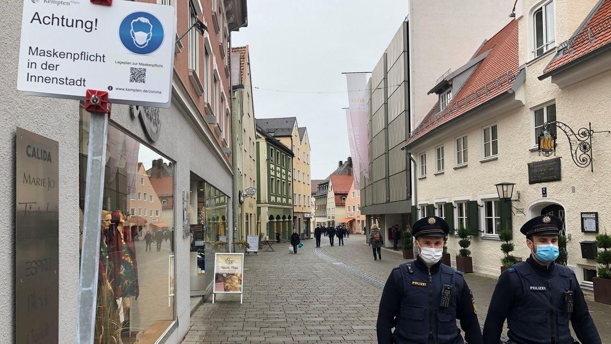 In der Innenstadt von Kempten weist ein Schild auf die Maskenpflicht hin. Zwei Polizeibeamte gehen Streife
