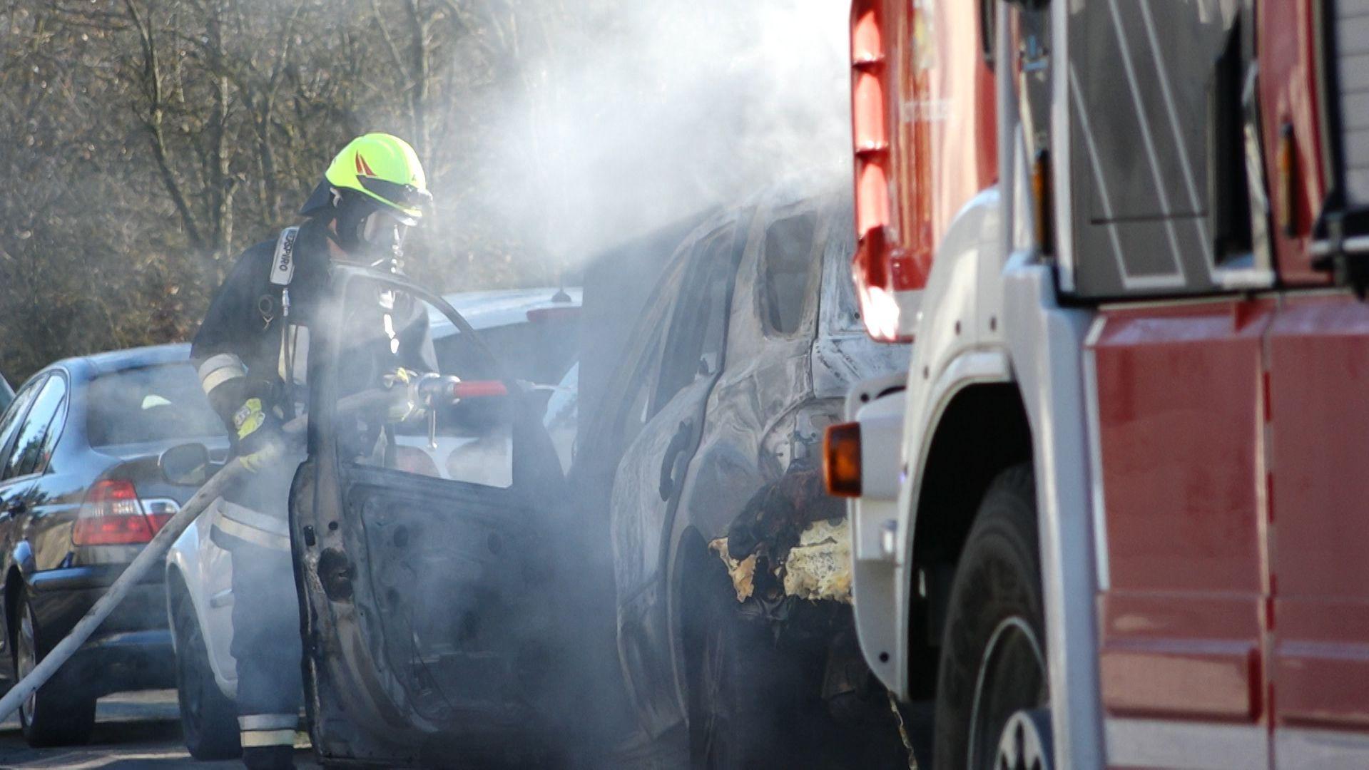 Ein Feuerwehrmann löscht ein qualmendes Auto, das gebrannt hat.