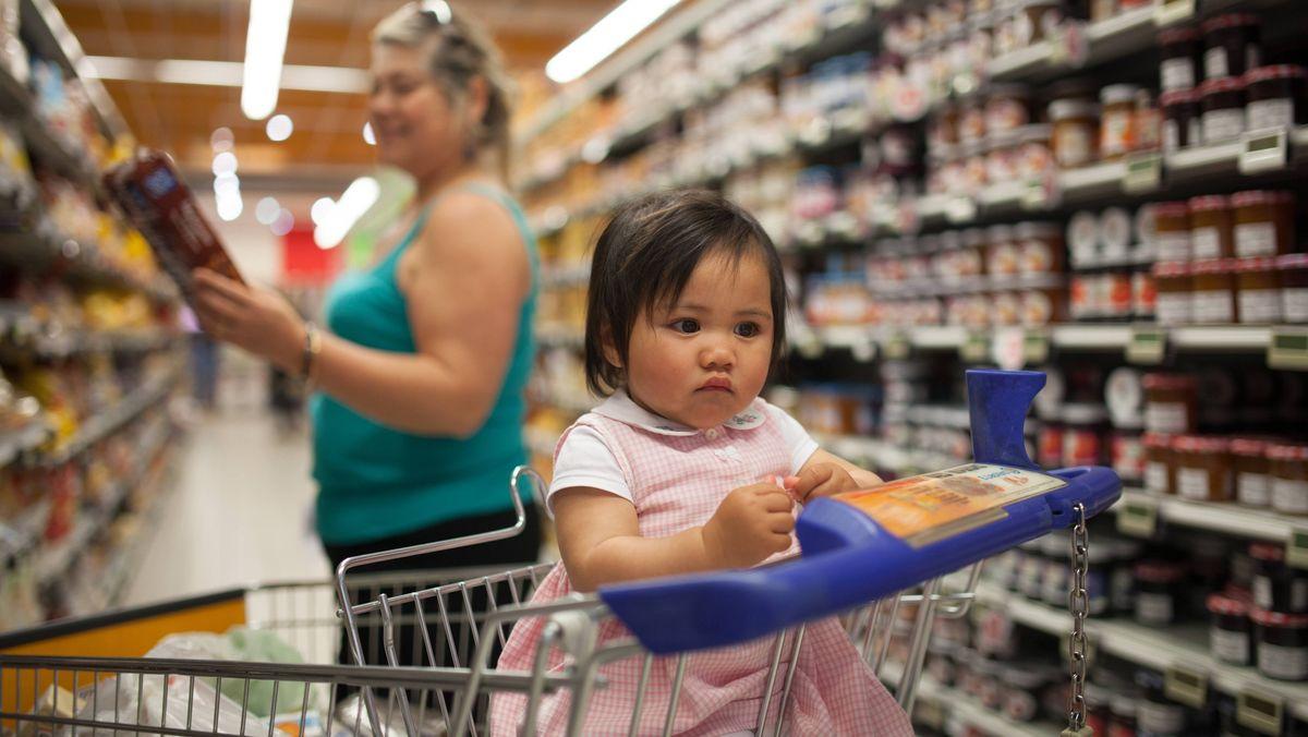 Symbolbild: Ein Kleinkind sitzt im Supermarkt in einem Einkaufswagen.