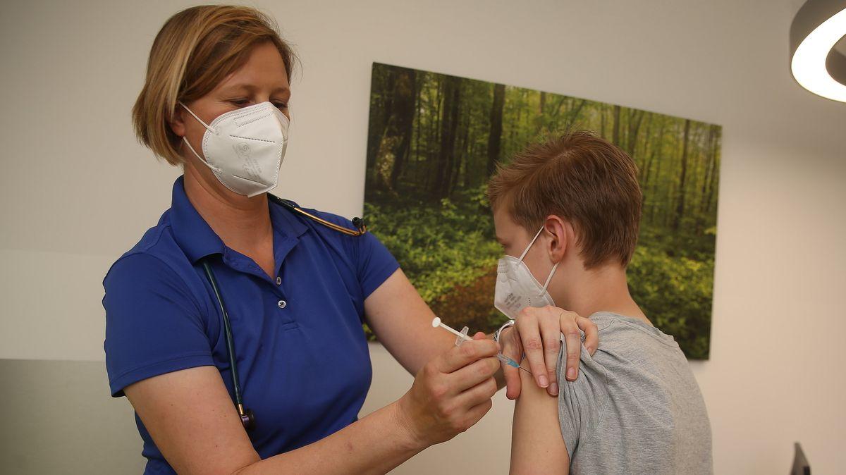 Eine Kinderärztin verabreicht einem Jungen eine Corona-Impfung.