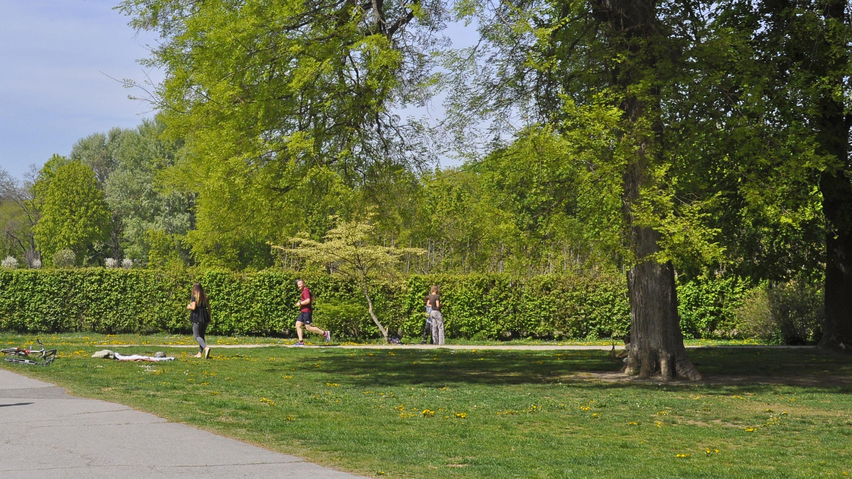Vereinzelte Spaziergänger oder Jogger auf einer grünen Wiese