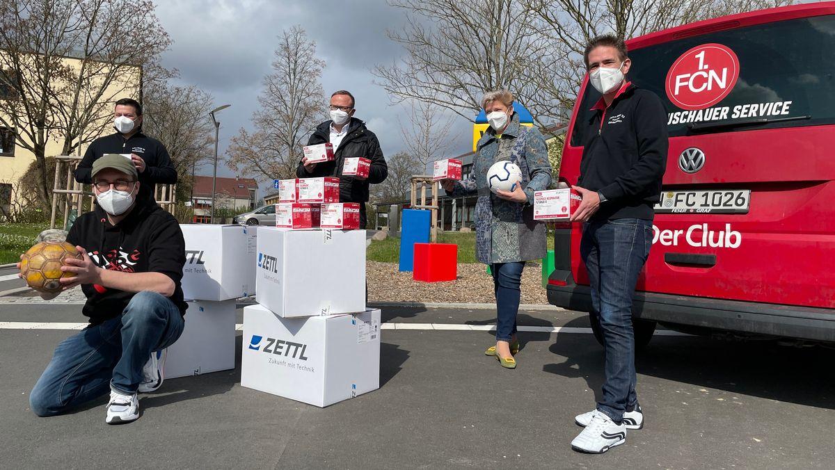 Clubfans mit Masken vor einem roten FCN-VW-Bus