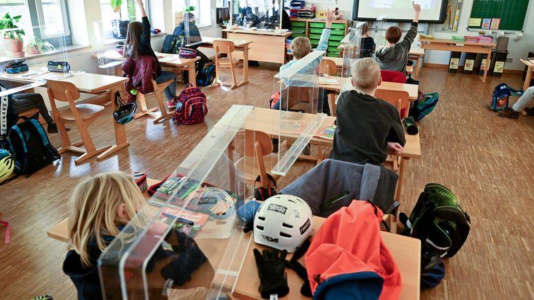 Kinder sitzen während des Unterrichts in einer Grundschulklasse mit Plexiglas-Trennscheiben zwischen den Plätzen an ihren Tischen.    Bild:picture alliance/dpa   Peter Kneffel