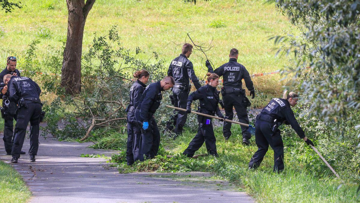 Polizisten durchsuchen Wiesen und Hecken am Rande eines Radweges in Bayreuth.