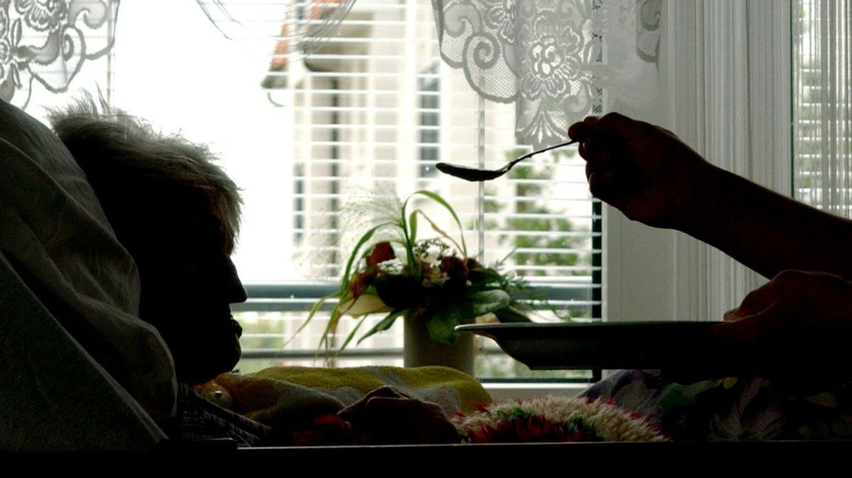 Im Schattenriß ist eine pflegebedürftige Frau zu sehen, die von einer Hand mit einem Löffel gefüttert wird.