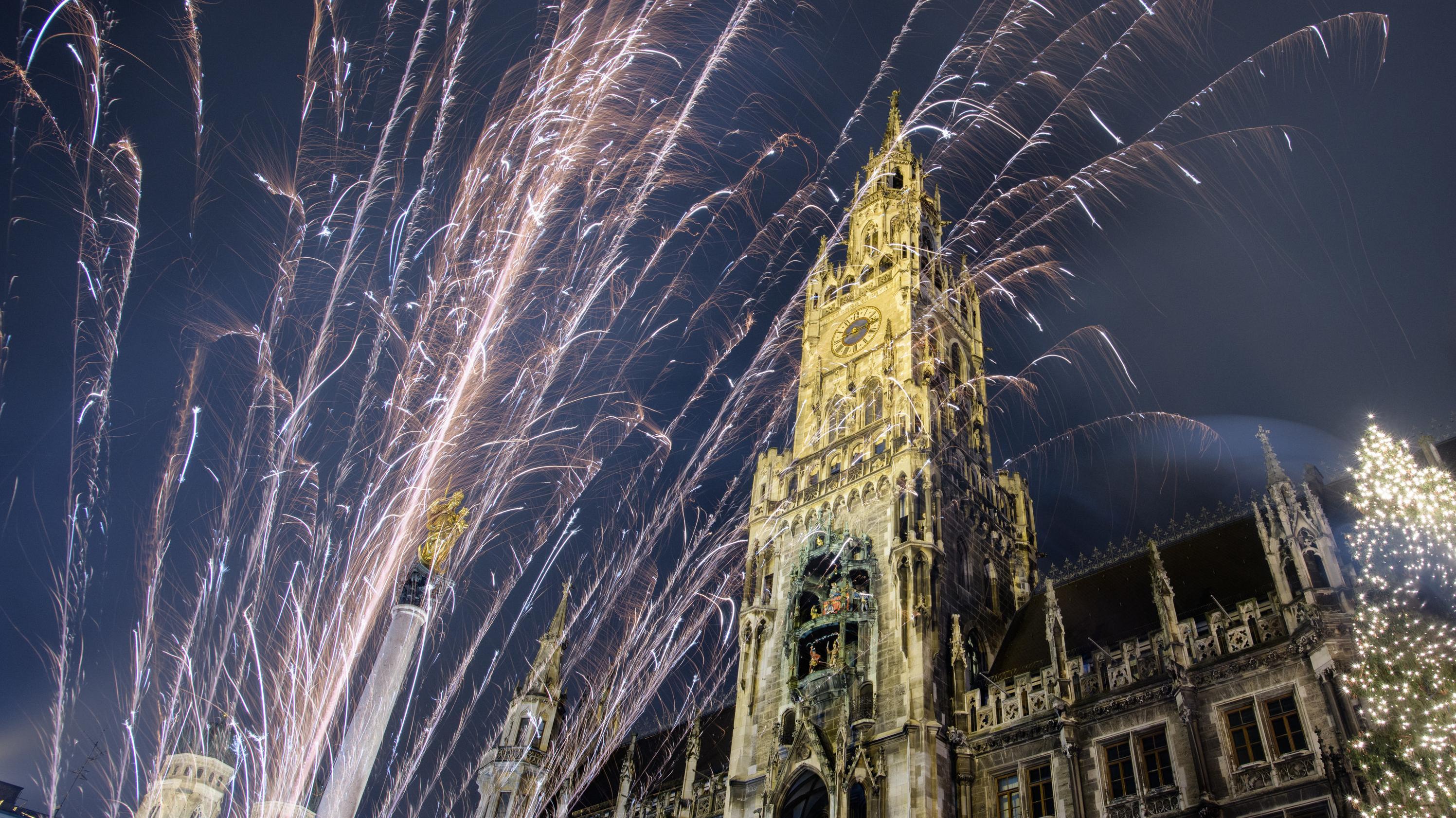 Feuerwerk sprüht vom Boden aus nach oben. Im Hintergrund das Rathaus von München.