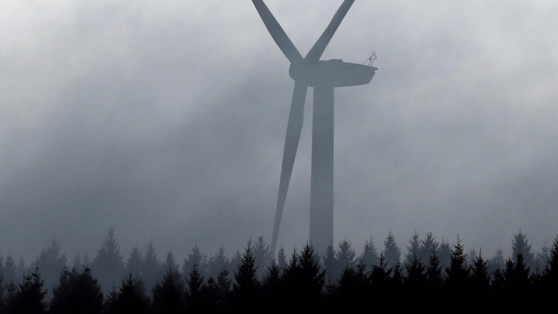 Ein Windrad ragt im Allgäu aus dem Nebel.