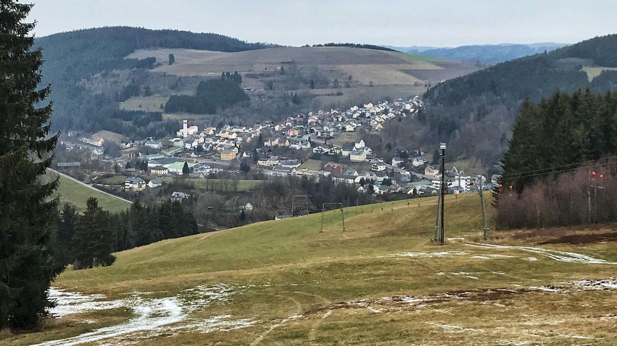 Nur ganz wenig Schnee liegt auf dem Hang neben dem Skilift, ansonsten ist nur grüne Wiese zu sehen, dahinter in Tal die Stadt Ludwigsstadt.