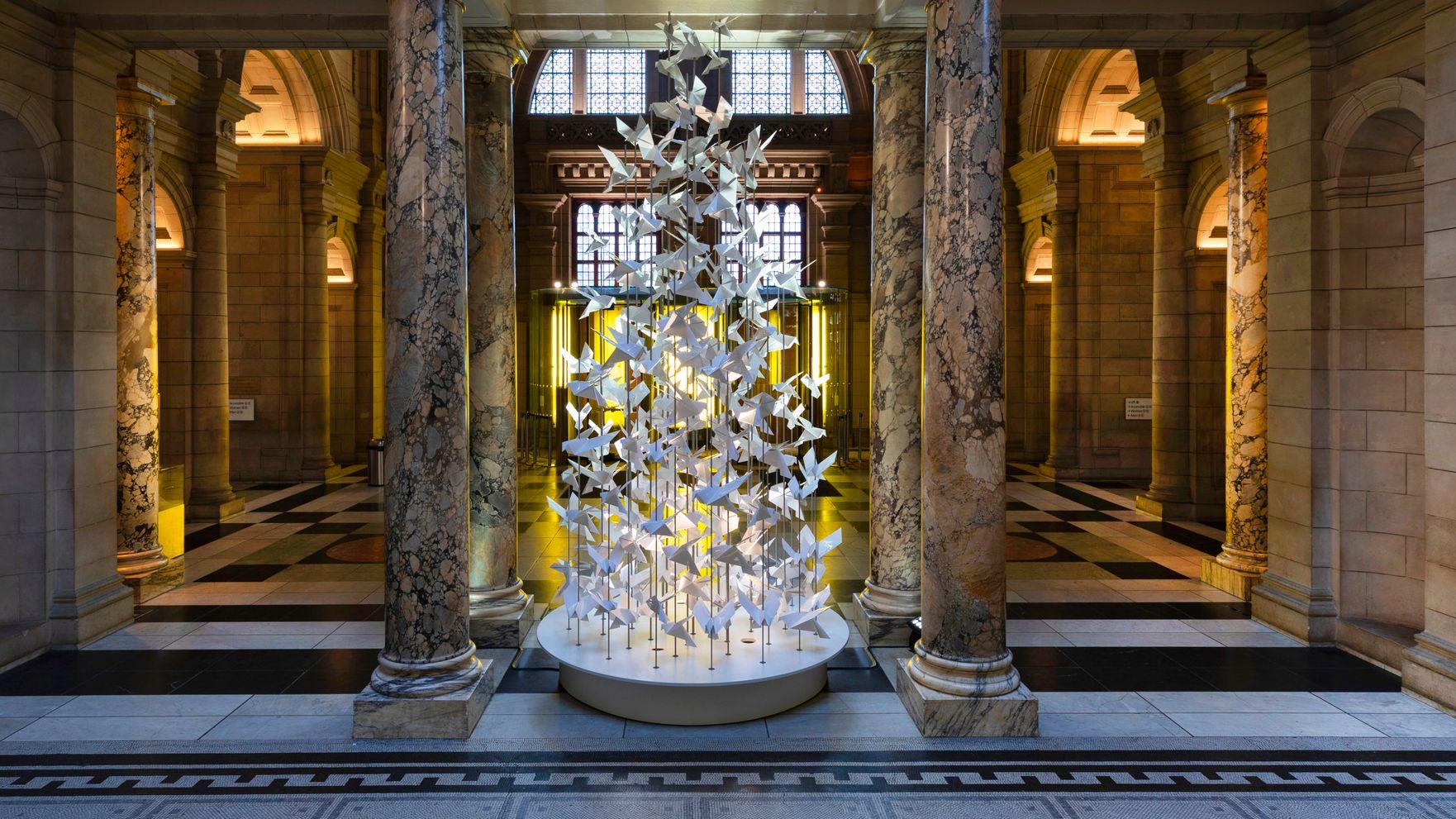 """Das Weihnachtsbaum Modell """"Freedom"""" von Anna Hünnerkopf besteht aus Papier-Friedenstauben und steht zwischen Marmorsäulen in der Eingangshalle des Museums"""