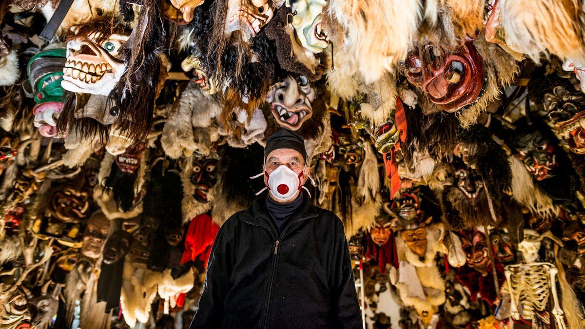 Ein Mann mit Mund-Nasen-Schutz steht unter einer Decke, von der etliche Masken hängen.