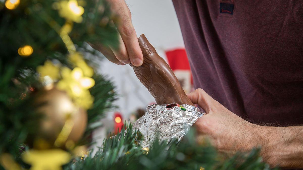 Männliche Hände packen vor einem Christbaum einen Schoko-Nikolaus aus